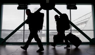 **FILE** Travelers walk to a ticketing desk at O'Hare International Airport in Chicago on Dec. 21, 2012. (Associated Press)