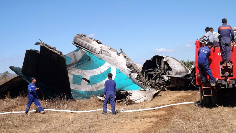 Members of a Myanmar Fire Brigade team gather near a damaged Air Bagan jetliner in Heho, Myanmar, on Tuesday, Dec. 25, 2012. The aircraft, packed with Christmas tourists, crash-landed into a rice paddy; two people were killed and 11 injured, officials said. (AP Photo)