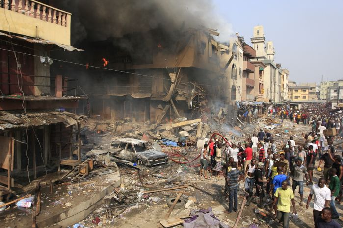 Onlookers gather at the site of a warehouse explosion and fire in Lagos, Nigeria, on Wednesday, Dec. 26, 2012.  (AP Photo/Jon Gambrell)