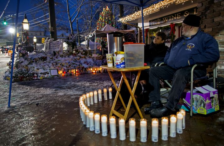 Joanne and Bill Brunetti of Newtown, Conn., part of a group monitoring memorials around the clock, take an early morning shift on Dec. 25, 2012, in Newtown, near a memorial for Sandy Hook Elementary School students and teachers. Gunman Adam Lanza walked into the school on Dec. 14 and opened fire, killing 26, including 20 children, before killing himself. (Associated Press)