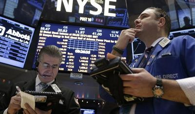 Daniel Kryger (left) and Kevin Lodewick Jr. follow trading from the floor of the New York Stock Exchange in New York on Dec. 26, 2012. (Associated Press)