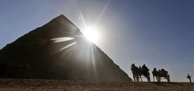 ** FILE ** Tourists ride in horse-drawn carriages past one of the Great Pyramids in Giza, Egypt, on Wednesday, Dec. 12, 2012. (AP Photo/Petr David Josek)