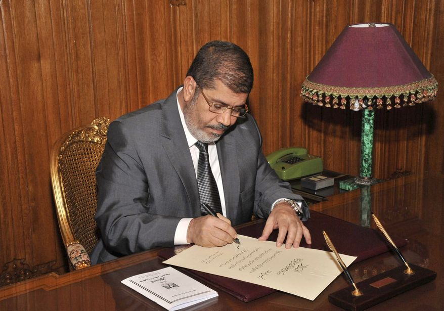 Egyptian President Mohammed Morsi signs into law the country's new Islamist-backed constitution late on Tuesday, Dec. 25, 2012. (AP Photo/Egyptian Presidency)