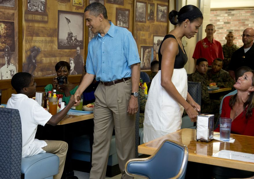 President Obama and first lady Michelle Obama visit with members of the military and their families in Anderson Hall at Marine Corp Base Hawaii on Tuesday, Dec. 25, 2012, in Kaneohe Bay, Hawaii. The first family is in Hawaii for a family holiday vacation. (AP Photo/Carolyn Kaster)