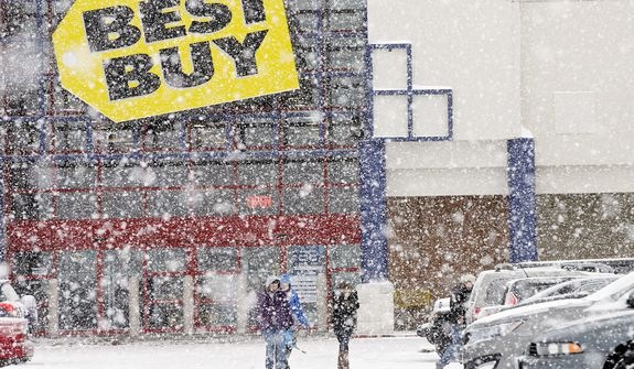 People walk in the parking lot of a Best Buy store during a severe snow storm in North Olmsted, Ohio Wednesday, Dec. 26, 2012. (AP Photo/Mark Duncan)