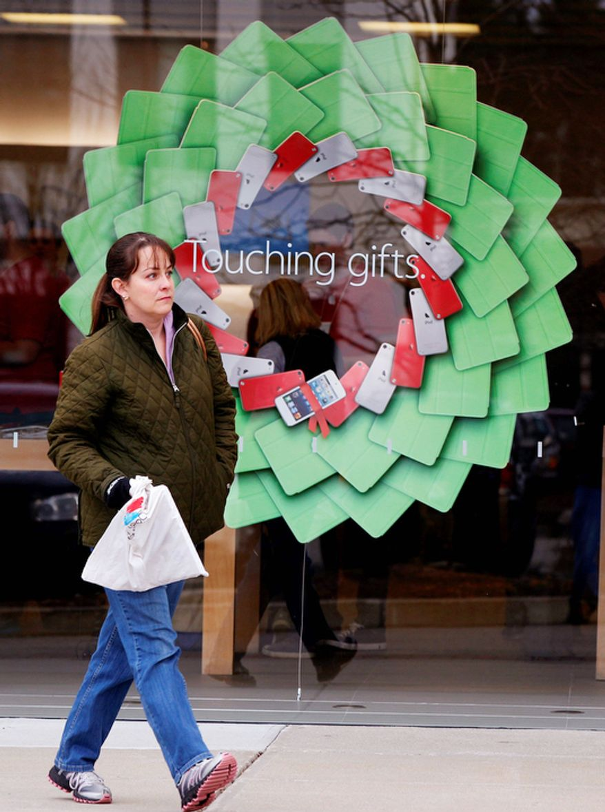 """A shopper carries a bag past a holiday display at the Apple Store at the Derby Street Shoppes in Hingham, Mass. Friday, Dec. 7, 2012. This holiday shopping season, stores haven't been offering the same big discounts as they did in previous years as they tried to lure shoppers in with other incentives, but during the final days leading up to Christmas, shoppers will see more of those jaw-dropping """"70 percent off"""" sale signs as stores try to salvage a season that so far has been disappointing. (AP Photo/Stephan Savoia)"""