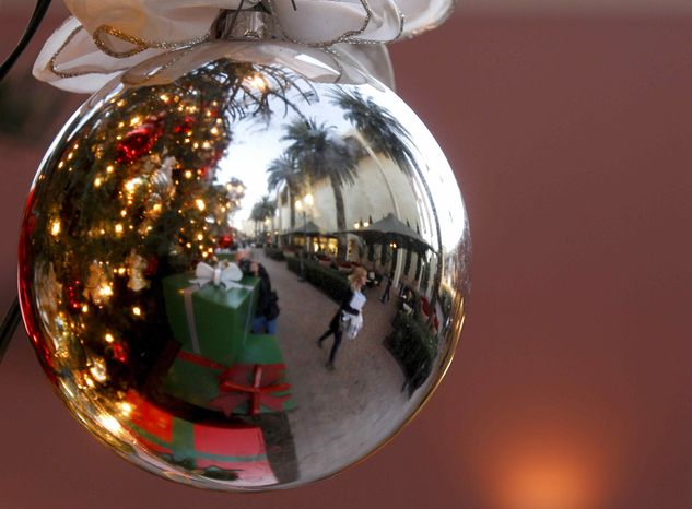 In this Thursday, Dec. 20, 2012, photo, a holiday shoppers reflected in a ornament handing from a large Christmas tree at Fashion Island shopping center in Newport Beach, Calif. Thursday, Dec. 20, 2012. U.S. holiday retail sales this year are the weakest since 2008, after a shopping season disrupted by storms and rising uncertainty among consumers. (AP Photo/Chris Carlson)