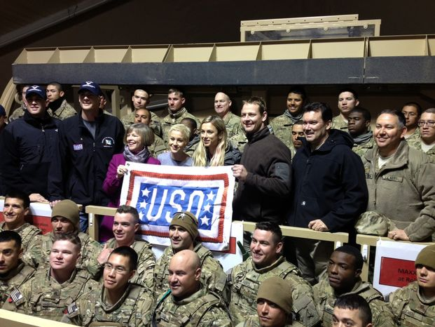 Washington Capitals player Matt Hendricks  holds the right corner of the USO banner in a picture with troops at Transit Center at Manas in Kyrgyzstan.  (Courtesy of Matt Hendricks)
