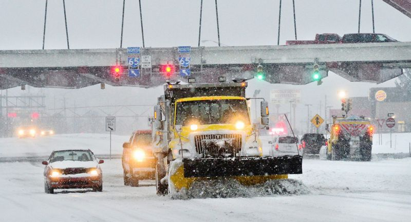 A Indiana State Highway Garage snow plows moves work along Jonathan Moore Pike in Columbus, Ind. Wednesday Dec. 26, 2012. The blizzard warning issued the day before by National Weather Service came to fruition in the region as winds picked up and snow began falling in earnest before dawn. (AP Photo/The Republic, Joe Harpring)
