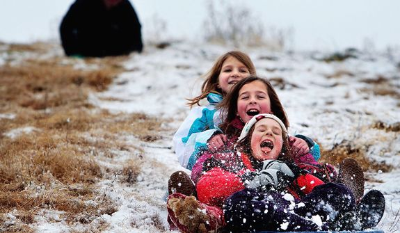 Elizabeth Seymour, 9, front, gets a mouthful of snow while sledding at the Colllierville, Tenn., landfill with Carly Catanzaro, 10, and her sister Ellery Seymour, 10, back, Wednesday Dec. 26, 2012. Shelby county managed to avoid the heavy snow that blanketed much of Arkansas, but that didn't stop the trio of sledders from taking advantage of the popular hill. (AP Photo/The Commercial Appeal, Jim Weber)