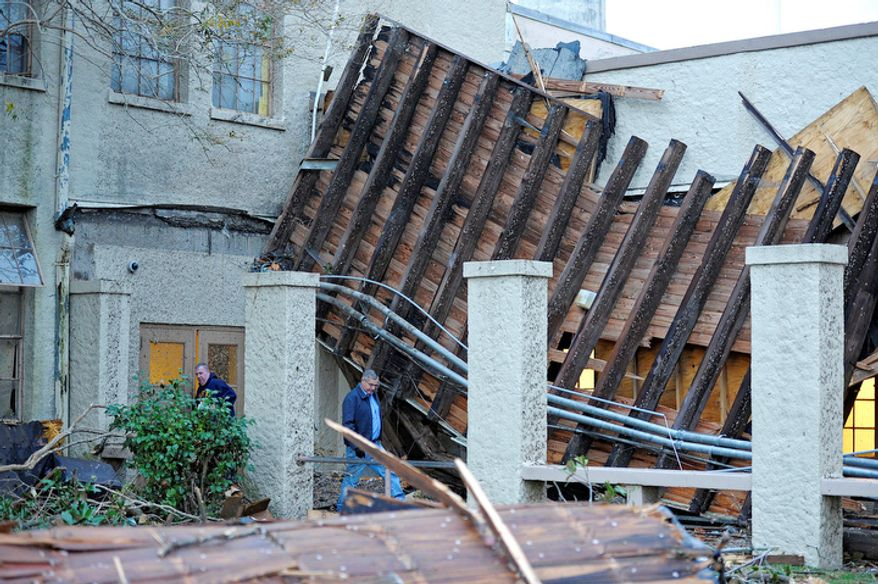 Murphy High School athletic custodian Mike Gill, left, and maintenance man Stewart Lynch, right, asses the damage caused to the school by a Christmas Day tornado as residents clean up at first light Wednesday, Dec. 26, 2012  in Mobile, Ala. (AP Photo/G.M. Andrews)