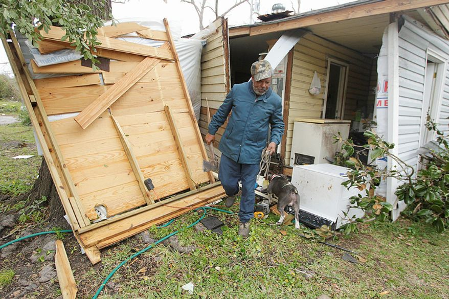 """Semler Street resident Mack Robinson checks on his tornado damaged home Wednesday, Dec. 26, 2012, in Prichard, Ala. Robinson's wife, Mary, was home when the tornado hit. """"Nobody got hurt, except my feelings,"""" Robinson said. (AP Photo/AL.com, Mike Kittrell)  MAGS OUT"""
