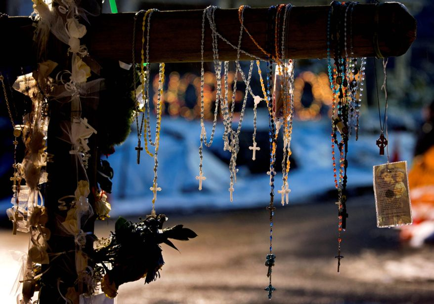 Rosaries and other religious items hang from a memorial in Newtown, Conn. Tuesday, Dec. 25, 2012. People continue to visit memorials in the wake of the shootings after gunman Adam Lanza walked into Sandy Hook Elementary School in Friday, Dec. 14, and opened fire, killing 26, including 20 children, before killing himself. (AP Photo/Craig Ruttle)