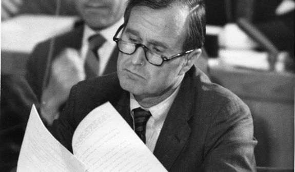 George Bush, U.S. Ambassador to the United Nations, looks through papers during the adoption of the agenda at the United Nations General Assembly at the headquarters in New York, Sept. 22, 1971.  The U.S. and 16 other countries called on the General Assembly to seat Communist China in the United Nations while permitting Nationalist China to remain.  (AP Photo)