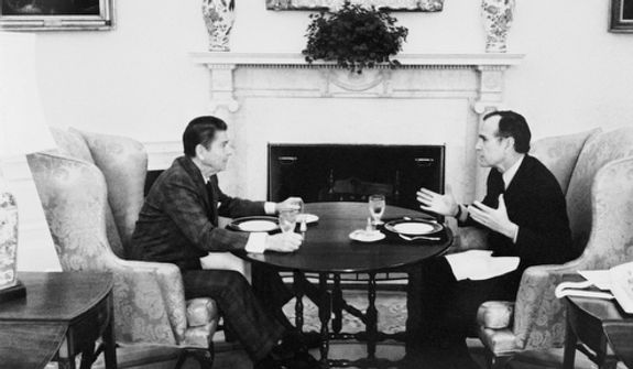 President Ronald Reagan and Vice President George Bush discuss the formation of the President's Task Force on Regulatory Relief, which will be headed by Bush, over lunch in the Oval Office at the White House in Washington on Thursday, Jan. 22, 1981. (AP Photo)