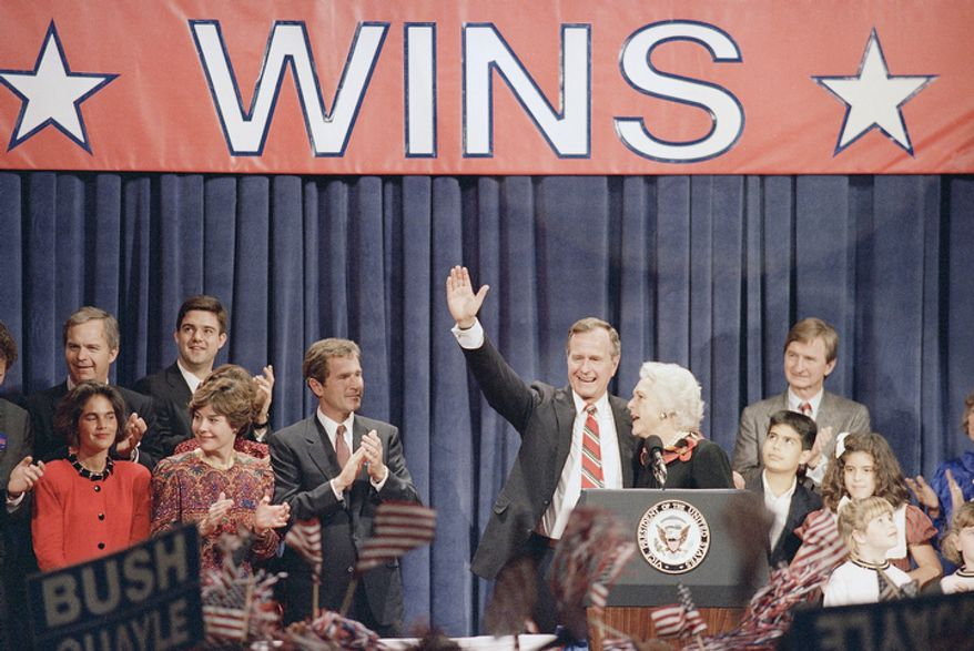 President-elect George Bush waves to the Houston rally honoring him while surrounded by his family after his election to the nation's top office, Nov. 9, 1988. (AP Photo)