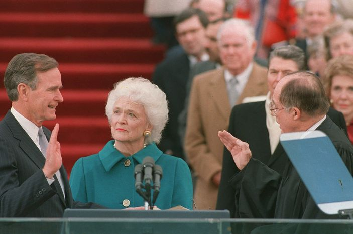 President George Bush raises his right hand as he is sworn into office as the 41st president of the United States by Chief Justice William Rehnquist outside the west front of the Capitol on Jan. 20, 1989.  First lady Barbara Bush holds the bible for her husband.  Former President Reagan is in the background.  (AP Photo/Bob Daugherty)