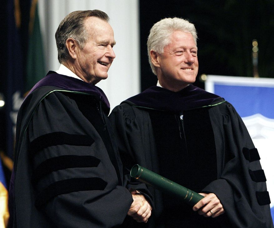 Former Presidents George H. W. Bush and Bill Clinton smile on the podium after receiving their honorary degrees at Tulane University Commencement in New Orleans on Saturday May 13, 2006. (AP Photo/Alex Brandon, Pool)