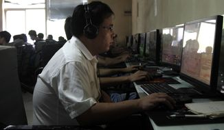 ** FILE ** A Chinese man uses a computer at an Internet cafe in Beijing in 2010. (Associated Press)