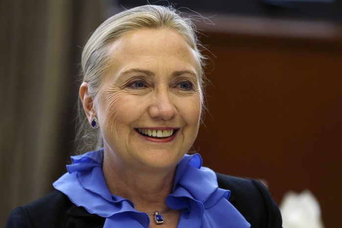 U.S. Secretary of State Hillary Rodham Clinton poses for photographs before a dinner hosted by K. Shanmugam, Singapore's minister for foreign affairs and minister for law, at the Ministry of Foreign Affairs in Singapore on Friday, Nov. 16, 2012. (Associated Press)