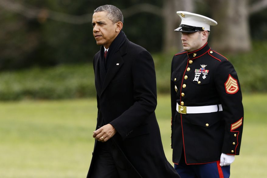 President Obama walks past a Marine honor guard as he steps off the Marine One helicopter and walks on the South Lawn at the White House in Washington on Dec. 27, 2012, as he returned early from his Hawaii vacation for meetings on the fiscal cliff. (Associated Press)