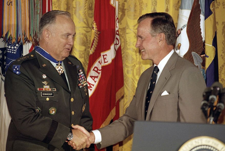 **FILE** President George Bush congratulates Desert Storm commander Gen. Norman Schwarzkopf after presenting him with the Medal of Freedom at the White House in Washington on July 4, 1991. (Associated Press)