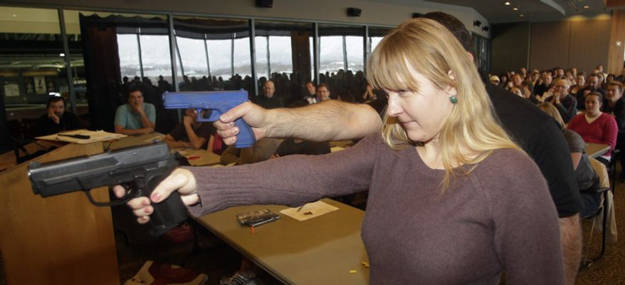 Clark Aposhian (rear), president of Utah Shooting Sport Council, demonstrates with a plastic gun while Joanna Baginska, a fourth-grade teacher at Odyssey Charted School in American Fork, uses a 40 cal. Sig Sauer on Dec. 27, 2012, during concealed-weapons training for 200 Utah teachers in West Valley City, Utah. The Utah Shooting Sports Council offered six hours of training in handling concealed weapons in the latest effort to arm teachers to confront school assailants. (Associated Press)