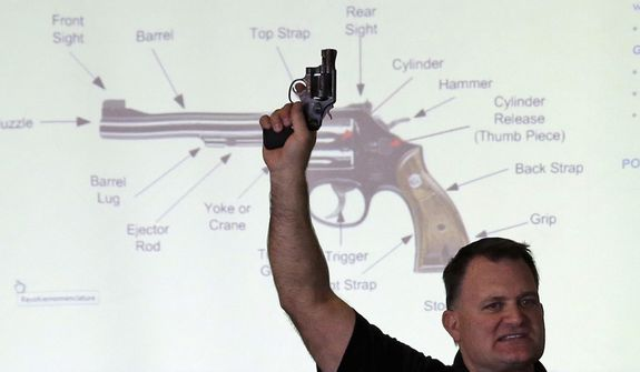 Clark Aposhian, president of Utah Shooting Sport Council, holds a pistol Dec. 27, 2012, during concealed-weapons training for 200 Utah teachers in West Valley City, Utah. The Utah Shooting Sports Council offered six hours of training in handling concealed weapons in the latest effort to arm teachers to confront school assailants. (Associated Press)