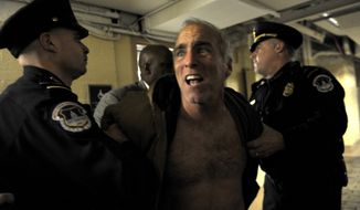Rives Grogan of Los Angeles, a pastor and anti-abortion protestor, is restrained by Capitol Hill police on Capitol Hill on Dec. 28, 2012, after demonstrating in the Senate Chamber visitor's gallery. (Associated Press)