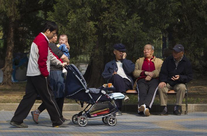**FILE** Elderly men rest on a bench April 28, 2011, as a family with their new born baby walk past at a park in Beijing. (Associated Press)
