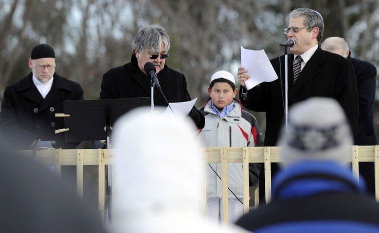 Rev. Mel Kawakami (center) of the Newtown United Methodist Church and Rabbi Shaul Praver (right) of Congregation Adath Israel in Newtown speak in Newtown, Conn., at an interfaith prayer vigil to remember the victims of the Sandy Hook Elementary School shootings on Dec. 28, 2012, two weeks after a gunman killed 20 children and six educators at the school. (Associated Press/Danbury News-Times)