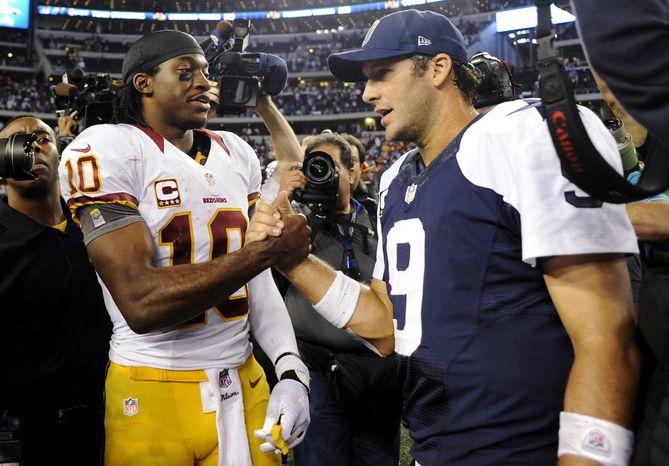 **FILE** Washington Redskins quarterback Robert Griffin III (10) and Dallas Cowboys quarterback Tony Romo (9) greet after the Redskins' 38-31 win in Arlington, Texas, on Nov. 22, 2012. (Associated Press)
