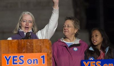 **FILE** Sarah Dowling (left) speaks Nov. 1, 2012, at a gay-marriage rally in Portland, Maine, accompanied by Linda Wolfe, her partner of 18 years, and their daughter, Maya Dowling-Wolfe. Dowling and Wolfe plan to marry after Maine passed a law allowing same-sex marriage, which takes effect at 12:01 a.m., Dec. 29, 2012. (Associated Press)