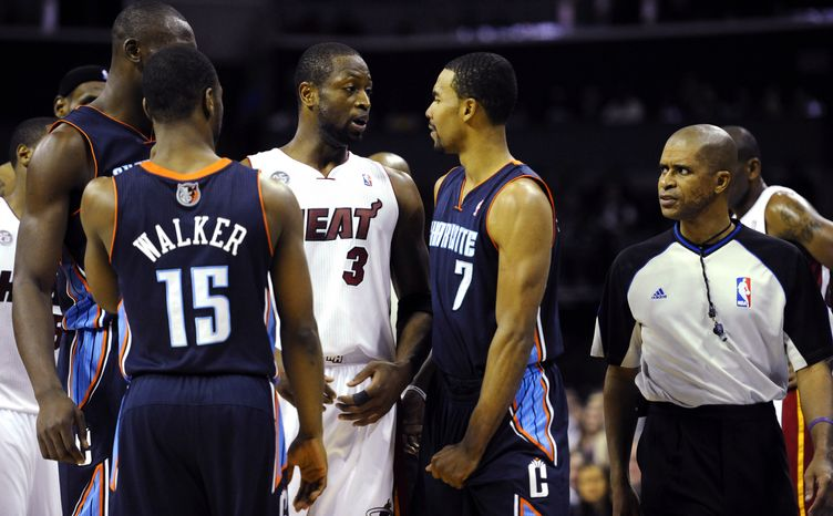 Miami Heat's Dwyane Wade (3) and Charlotte Bobcats' Ramon Sessions (7) interact after Sessions was called for a foul as referee Zach Zarba watches during the second half of the Heat's 105-92 win on Dec. 26, 2012, in Charlotte. (Associated Press/The Charlotte Observer, David T. Foster III)