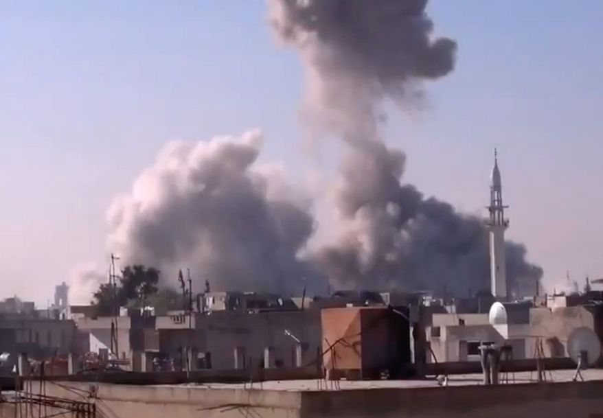 In this image taken from video obtained from the Shaam News Network, which has been authenticated based on its contents and other AP reporting, smoke rises from buildings from heavy shelling in Homs, Syria, on Dec. 27, 2012. (Associated Press/Shaam News Network via AP video)