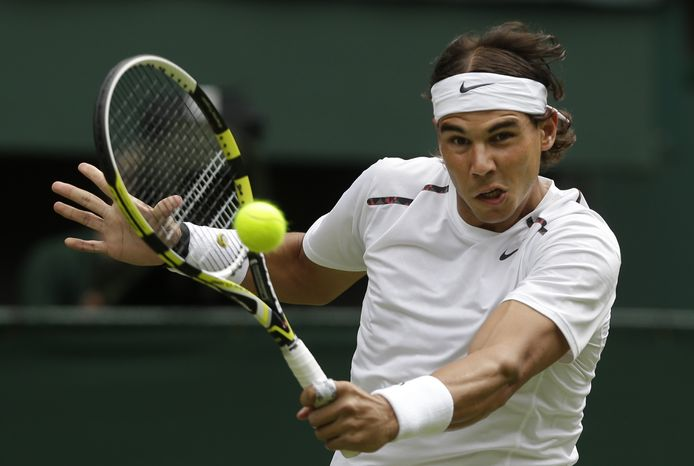 **FILE** Rafael Nadal returns a shot to Thomaz Bellucci during a first-round men's singles match at the All England Lawn Tennis Championships at Wimbledon on June 26, 2012. (Associated Press)