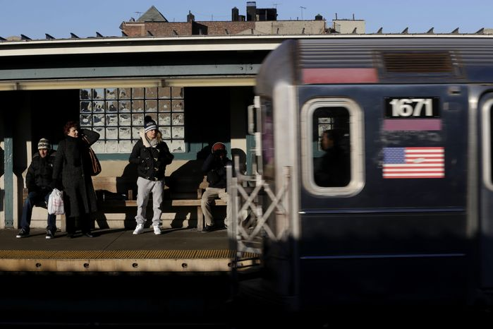 ** FILE ** Commuters watch as a train enters the 40th St-Lowry St Station, where a man was killed after being pushed onto the subway tracks, in the Queens section of New York, Friday, Dec. 28, 2012.  (AP Photo/Seth Wenig)