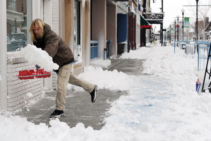 Scott Becker shovels the sidewalks of businesses along Main Street in downtown Evansville, Ind., on Dec. 27, 2012. (Associated Press/The Evansville Courier & Press)