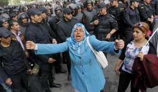 An Egyptian woman shouts anti-Mohammed Morsi slogans as soldiers block a road leading to the Shura Council where the president addressed the upper house of parliament in Cairo, Egypt, Saturday, Dec. 29, 2012. Egypt's Islamist president warned Saturday against any unrest that could harm the drive to repair the country's battered economy in a sharply worded speech that urged the opposition to work with his government. (AP Photo/Amr Nabil)