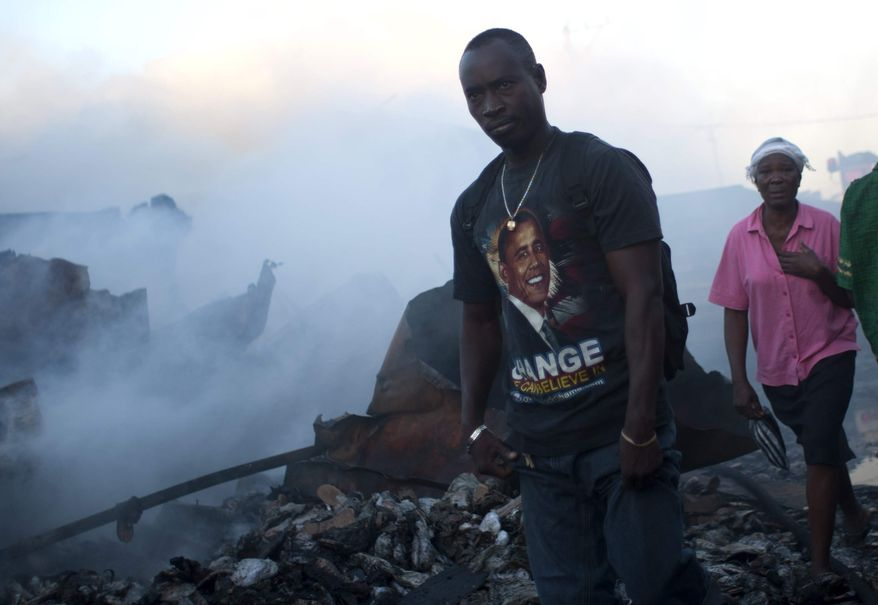 People walk by the remains of a market burned in an overnight fire in the Haitian capital's Market District in Port-au-Prince, Haiti, Saturday, Dec. 29, 2012. The market is one of several that have burned over the past year. (AP Photo/Dieu Nalio Chery)