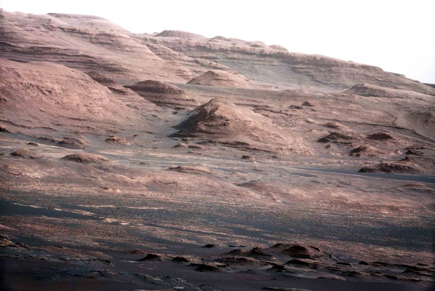 ** FILE ** This file image provided by NASA shows the base of Mount Sharp on Mars. The Curiosity rover is set to drive toward the mountain in mid-February after drilling into a rock. The image was taken by Curiosity's 100-millimeter Mast Camera on Aug. 23, 2012. Scientists enhanced the color in one version to show the Martian scene under the lighting conditions we have on Earth, which helps in analyzing the terrain. (AP Photo/NASA/JPL-Caltech/MSSS, File)