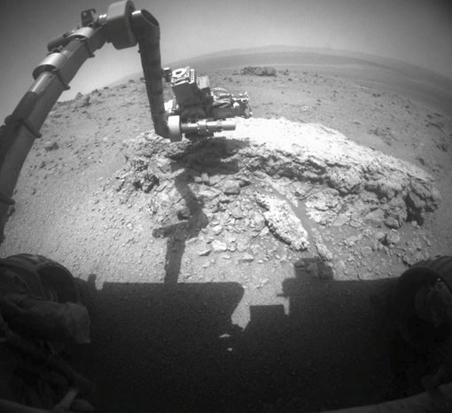 """This image provided on Thursday, Sept. 1, 2011, by NASA shows the agency's Mars Exploration Rover Opportunity using its camera to take this picture showing the rover's arm extended toward a light-toned rock, """"Tisdale 2,"""" during the 2,695th Martian day on Aug. 23, 2011. The solar-powered rover beamed back images of the horizon, soil and nearby rocks that are unlike any it has seen during its seven years roaming the Martian plains. (AP Photo/NASA)"""