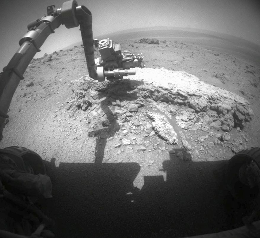"This image provided on Thursday, Sept. 1, 2011, by NASA shows the agency's Mars Exploration Rover Opportunity using its camera to take this picture showing the rover's arm extended toward a light-toned rock, ""Tisdale 2,"" during the 2,695th Martian day on Aug. 23, 2011. The solar-powered rover beamed back images of the horizon, soil and nearby rocks that are unlike any it has seen during its seven years roaming the Martian plains. (AP Photo/NASA)"