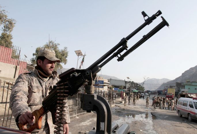 An Afghan police officer stands guard at the border crossing with Pakistan on Saturday east of Kabul. Violence in Afghanistan fell in 2012, but insider killings by uniformed Afghans against their foreign allies rose dramatically. (Associated Press)