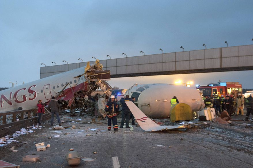 Rescuers work at the site where a plane careened off the runway at Vnukovo Airport in Moscow on Saturday, Dec. 29, 2012. The Tu-204 aircraft belonging to the Russian airline Red Wings broke into pieces and caught fire, killing five people. (AP Photo/Alexander Usoltsev)