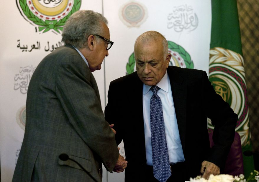 Lakhdar Brahimi (left), the U.N.-Arab League envoy to Syria, shakes hands with Arab League Secretary-General Nabil Elaraby following a joint press conference at the league's headquarters in Cairo on Sunday, Dec. 30, 2012. (AP Photo/Nasser Nasser)
