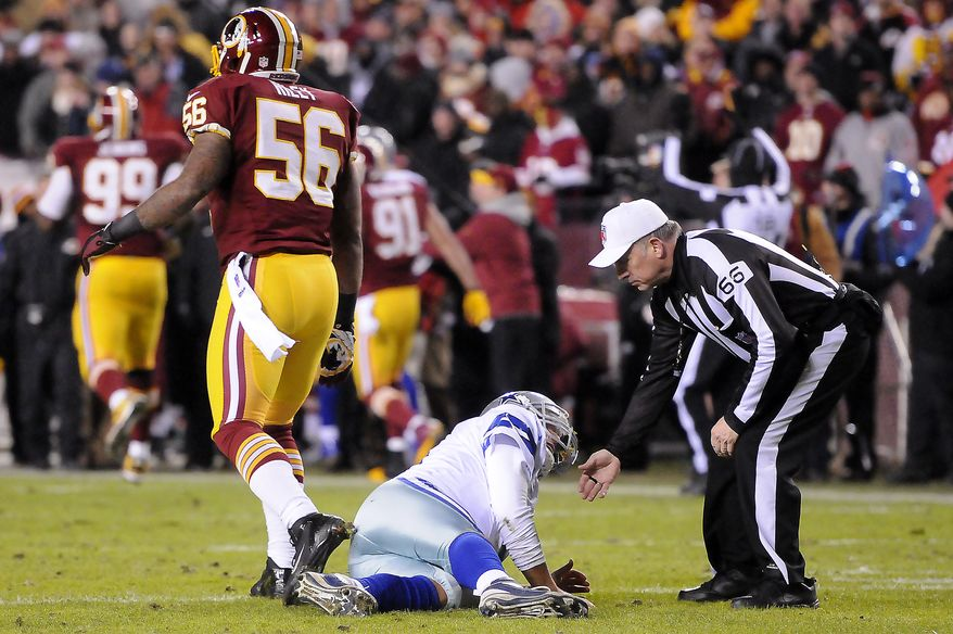 Dallas Cowboys quarterback Tony Romo (9) looks to referee Walt Anderson (66) after being knocked to the ground by Washington Redskins inside linebacker Perry Riley (56) at FedEx Field, Landover, Md., Dec. 30, 2012. (Preston Keres/Special to The Washington Times)