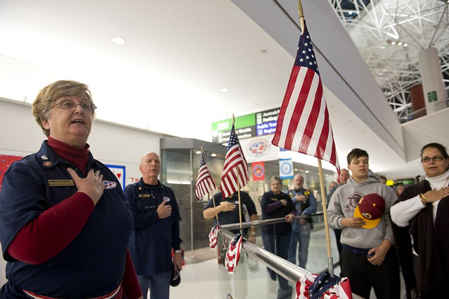 Operation Welcome Home Maryland team leader Anne Church, left, leads volunteers and friends and family in the Pledge of Allegiance before the arrival of a Delta charter flight bringing troops home at BWI Thurgood Marshall Airport in Baltimore, Md. on Friday, Dec. 28, 2012. There were 362 people on the Delta charter flight, which made several stops in the mid-East and Ramstein Air Force Base in Germany before bringing people home. More flights came in over the weekend. (Barbara L. Salisbury/The Washington Times)