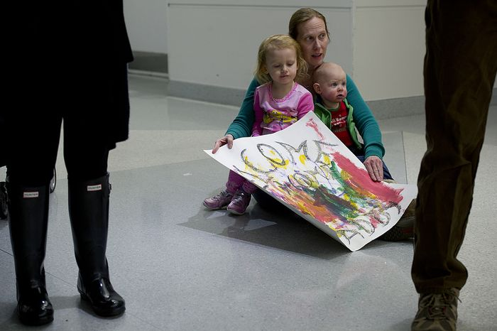 Cheryl Lauer of Alexandria, Va. sits with her 2 1/2-year-old daughter Lauren and 10-month-old son Drew on the floor of BWI Thurgood Marshall Airport Friday, Dec. 28, 2012 as they await the arrival of their dad/husband on a military charter flight. Flights came in all weekend long, bringing several hundred troops and military contractors back to the United States in time for the new year. (Barbara L. Salisbury/The Washington Times)
