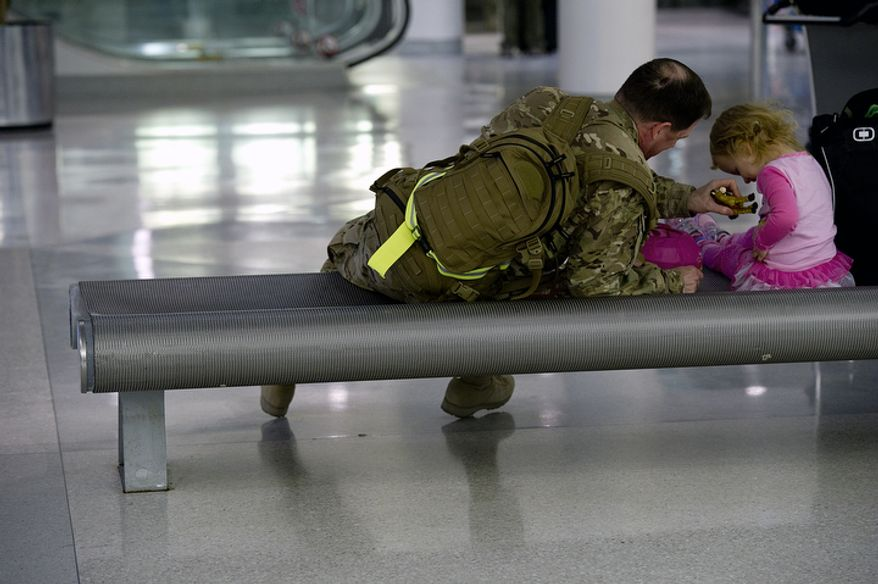 Drew Lauer of Alexandria, Va. plays with his 2 1/2-year-old daughter Lauren at BWI Thurgood Marshall Airport Friday, Dec. 28, 2012 after arriving home from a six-month deployment in Qatar. (Barbara L. Salisbury/The Washington Times)